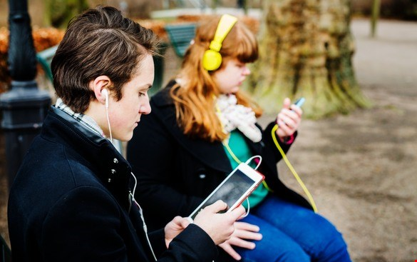 Teenagers reading with smartphone and tablet