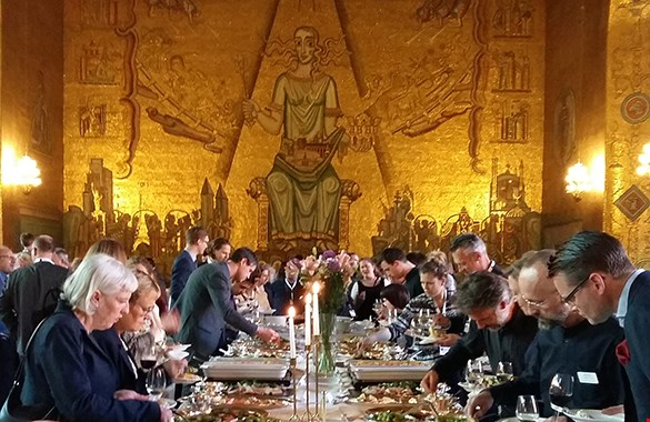 A picture from a dinner in the City Hall with a large golden wall in the back.