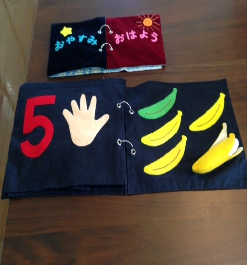 Tactile cloth book: The number 5, a hand showing 5 fingers and five bananas.